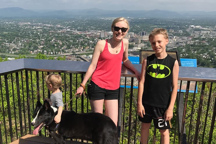 Rachel with her kids and two dogs on a balcony