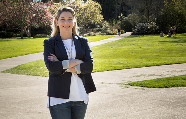 Kathryn Cowsert stands in the Memorial Union quad on the OSU campus smiling with her arms crossed. She wears a white shirt and black blazer.