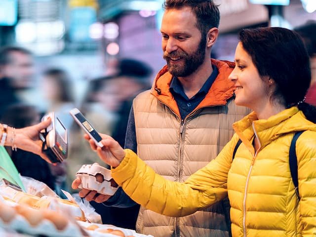 a woman uses a handheld device to complete a transaction at a busy market