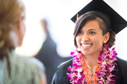 OSU graduate wearing a mortarboard and colorful lei
