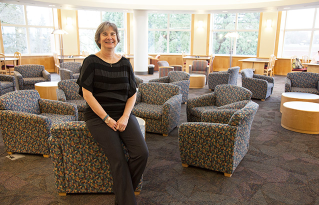 Joan Oakes, Ecampus student services specialist, sits against the back of a short cushioned chair in the OSU Valley Library. She smiles and wears a black and gray striped shirt.