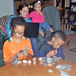 Carol works on a geology assignment in her living room while her three children experiment with the rocks in the lab kit.