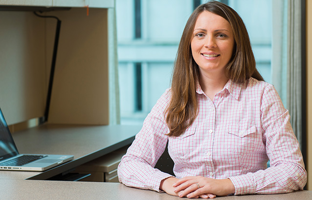 Kathleen Garney, an Ecampus student in the MBA in Executive Leadership track, sits at a desk with her hands resting atop it.