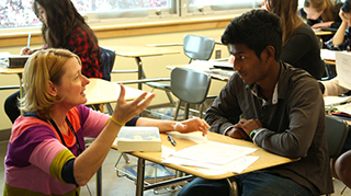 A teacher talks with an English language learning student about an essay he is writing.