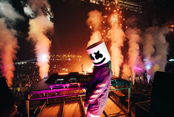 Masked performer on stage with pyrotechnics behind