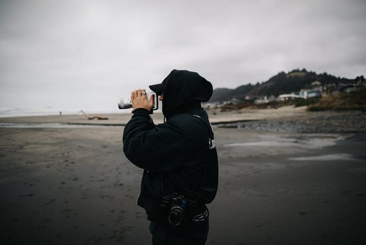 Hooded figure on a beach holding a camera
