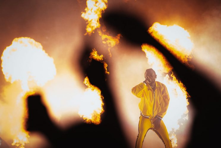 Performer Kendrick on stage with fire all around